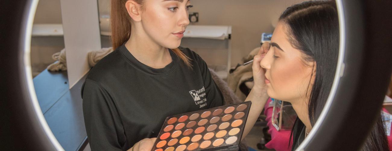 Student applying makeup to model