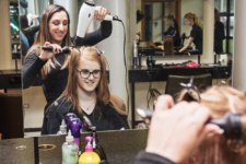 Female hairdressing student gives client blow dry limavady campus