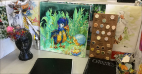 Art & Design student's desk with paintings and sculptures