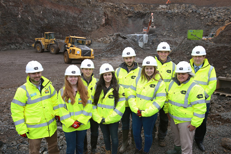 Group of contstruction students on building site wearing high vis jackets and protective helmets