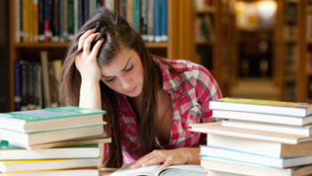 Female young adult student sitting at table in library reading a book, piles of books on table