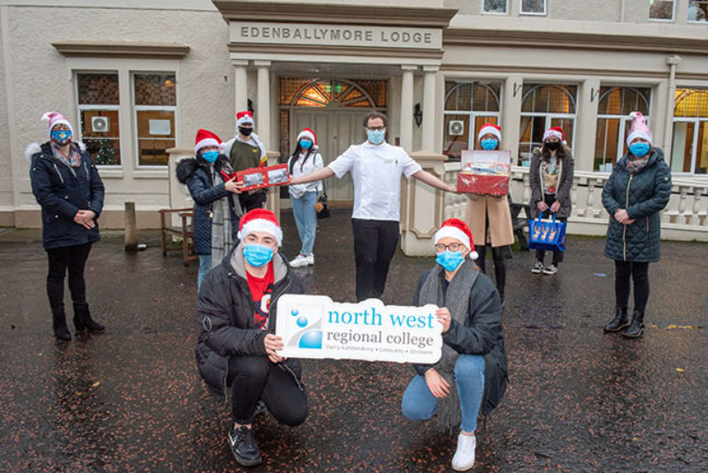 Group of students standing outside care home wearing Santa hats and face coverings