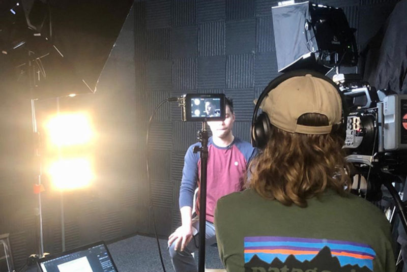 Two male students in film studio with camera and lighting equipment