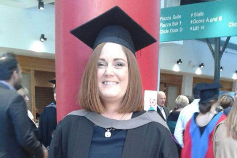 NWRC student smiling at graduation ceremony wearing graduation robes and mortarboard
