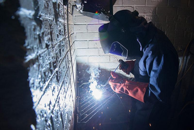 Welder in protective clothing, welding in workshop